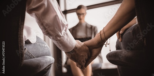 Fototapeta Couple holding hands with marriage counselor