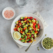 Avocado, black bean, corn and bell pepper salad in white bowl