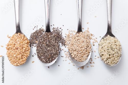 Photo semillas de sesamo, chia, lino y cañamo en cuchara sobre fondo blanco