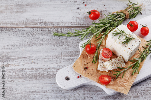 Plakat Świeży feta ser z rozmarynami na białej drewnianej porci desce