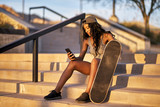 young african american woman with skateboard using smart phone at park while resting on steps