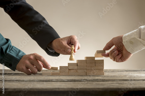 Fototapety, obrazy: Business teamwork concept with a businessman moving a chess piece up a series of steps