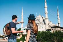 A Couple Of Tourists A Young Man And A Pretty Woman Look At The Map Next To The World-famous Blue Mosque Also Called Sultanahmet In Istanbul, Turkey. A Man Shows His Hand Direction.