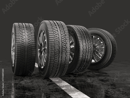 Fotografía  Four car tires rolling on a road on a gray background.