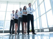 Smiling and confident business team standing in front of a bright