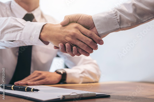 Fototapeta Estate broker agent and customer shaking hands after signing contract documents for realty purchase mortgage loan approval obraz