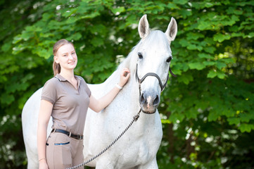 Portrait of beautiful white horse with pretty young teenage girl