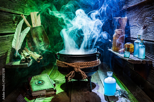 Photo  Vintage witcher cauldron with magic potions and books for Halloween