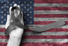 USA United Stated Of America 9/11 Memorial, Patriot Day And National POW/MIA Recognition Day Concept With Black Awareness Ribbon On People's Hand Support On American Flag