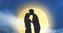 Silhouettes Of A Young Couple Under The Starry Sky With Full Moon.