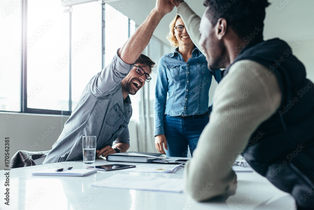 Fototapety, obrazy: Two colleagues giving high five during meeting