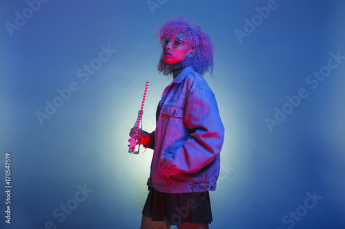 Valokuva  vintage black woman with trendy clothes drinking a soda on neon lights