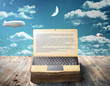 Leinwanddruck Bild - The concept of e-book. An open book as laptop lies on a wooden table against the sky. Writing.