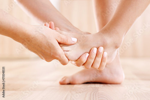 Fototapeta Masaż stopy dziecka. Kobieta rozmasowuje stopę dziecka.