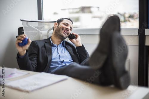 Fotografie, Obraz  Manager seduto comodamente nel suo ufficio, con i piedi sopra la  scrivania parl