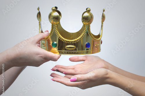 Fényképezés Hands gives the golden crown as symbol of power to another person