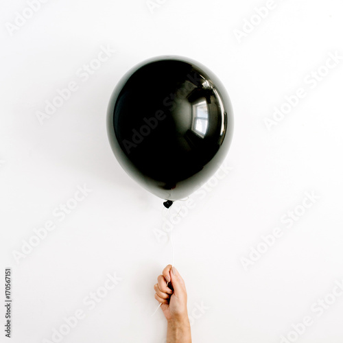 Foto op Canvas Ballon Halloween minimal concept. One black balloon in girl's hand. Flat lay, top view.