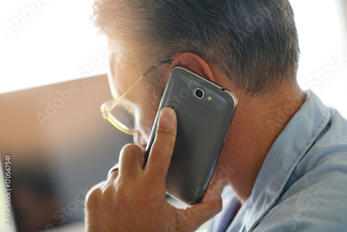 Fotografiet  Closeup of mature man holding smartphone to ear