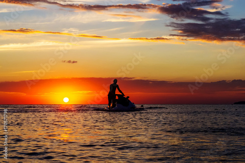 silhouette of a man on a jet ski in the sun