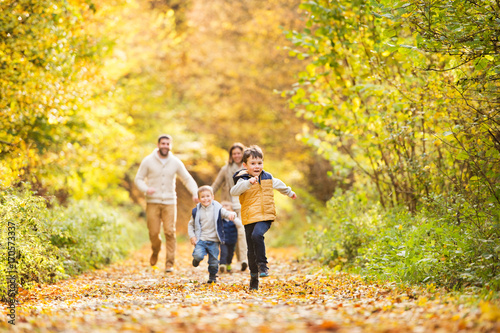 Obraz Beautiful young family on a walk in autumn forest. - fototapety do salonu
