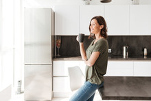 Side View Of Smiling Casual Woman Drinking Coffee On Kitchen