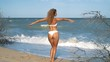 Young beautiful sexy tanned girl in bikini with curly hair sitting on the beach at sunset by the sea. She smiled enigmatically, stroked herself and. Slow motion. 120fps