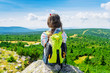 Young travel girl sitting on the rock mountain with backpack, relaxing