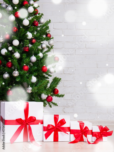 christmas background gift boxes under decorated christmas tree and flying snow