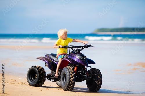 Child on quad bike at beach. All-terrain vehicle.