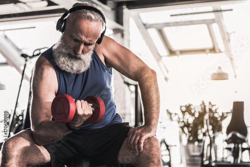 Confident old pensioner is spending time in gym