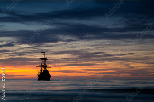 Photo Stands Ship Pirate ship in sunset scenery.