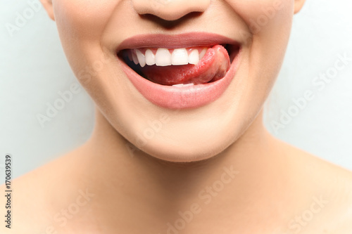 Young smiling woman licking her teeth on light background, closeup Fototapete