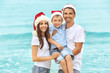 Young couple with boy on beach. Christmas concept