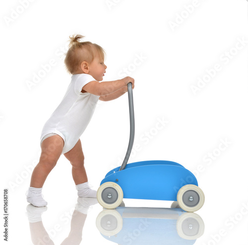 Photo  Small smiling baby girl toddler with toy walker make first steps i