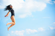 A young woman in tights is engaged in gymnastics and jumps, drains, leads herself into a good shape. Pleasure from training. Girl jumping against the sky