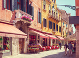 Fototapeta Uliczki - Colorful cozy street with tables of cafe at  a sunny morning, Venice, Italy.    Toned image