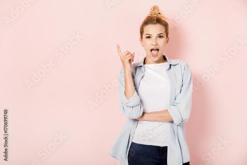 Fotografia  Młoda blondynki dziewczyna z pomysłem na różowym tle