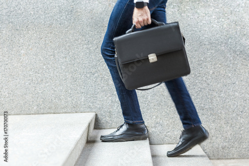Photo Businessman with briefcase in hand walking up on stairs.