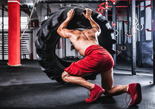 Muscular Athletic Bodybuilder Flipping Tire In Cross Gym