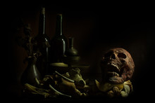 Still Life Skull , Bone ,Wine Bottles And Flower On Old Wood Table Background -Halloween Or Esoteric Concept