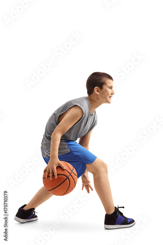 Profile shot of a boy dribbling a basketball