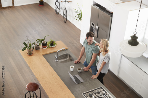 Fotografie, Obraz  Overhead View Of Couple Looking At Laptop In Modern Kitchen