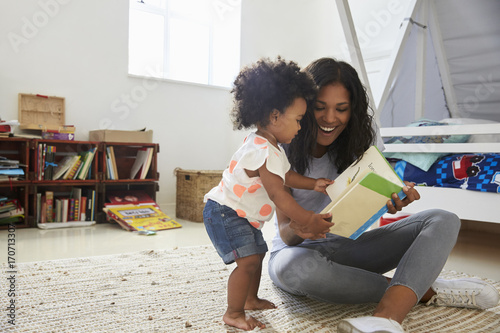 Valokuva Mother And Baby Daughter Reading Book In Playroom Together