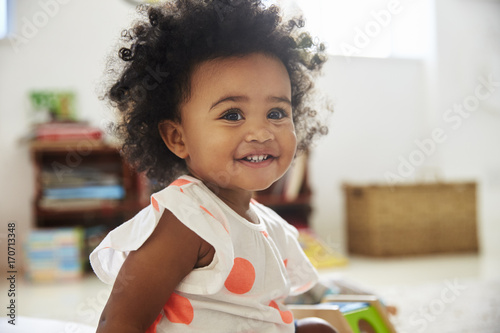 Happy Baby Girl Playing With Toys In Playroom Poster