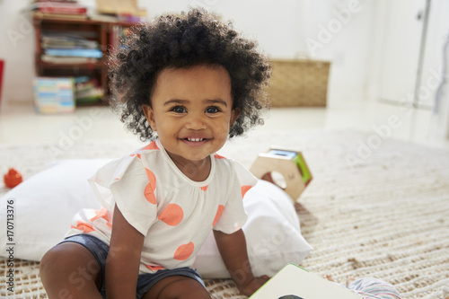 Portrait Of Happy Baby Girl Playing With Toys In Playroom Canvas Print