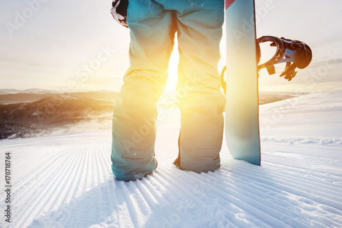 Closeup snowboarder at ski slope with snowboard
