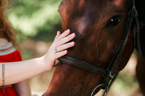Cuadros en Lienzo  Summer day on the farm. Young woman caress horse.