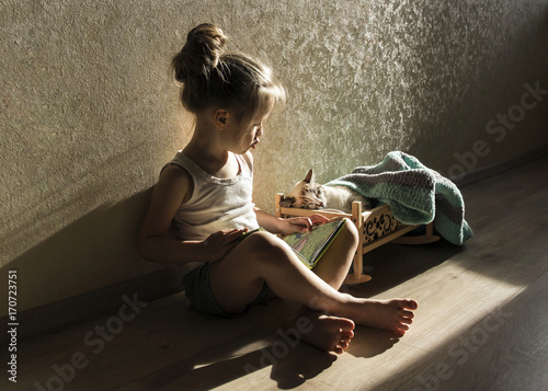 dziewczynka-czytajaca-bajke-swojemu-kotu-spiacemu-w-lozeczku
