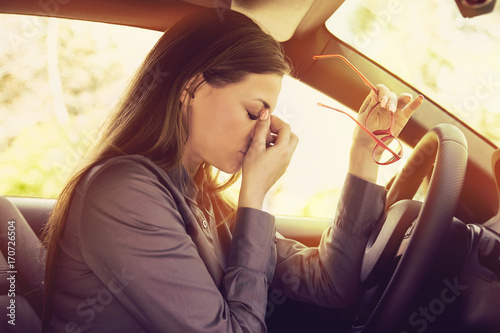 Photo Woman having headache taking off glasses has to make a stop after driving car in
