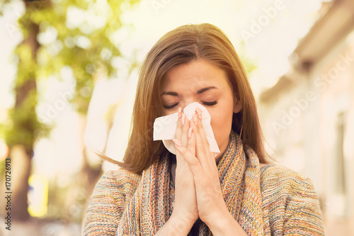 Photo Woman with allergy symptoms blowing nose